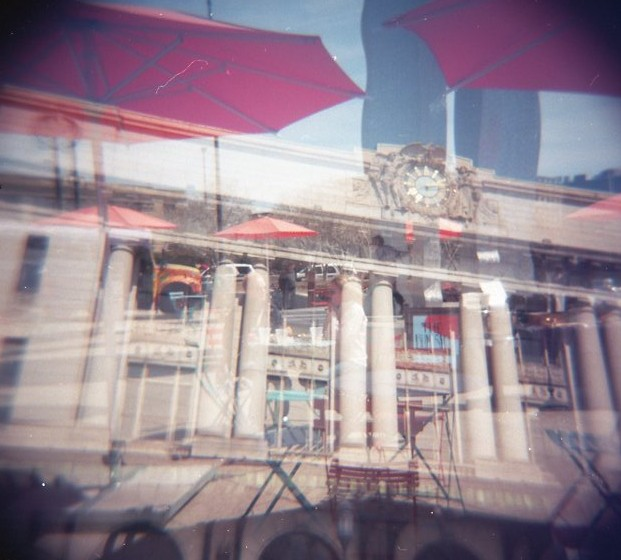 Double exposure of Penn Station and umbrellas.