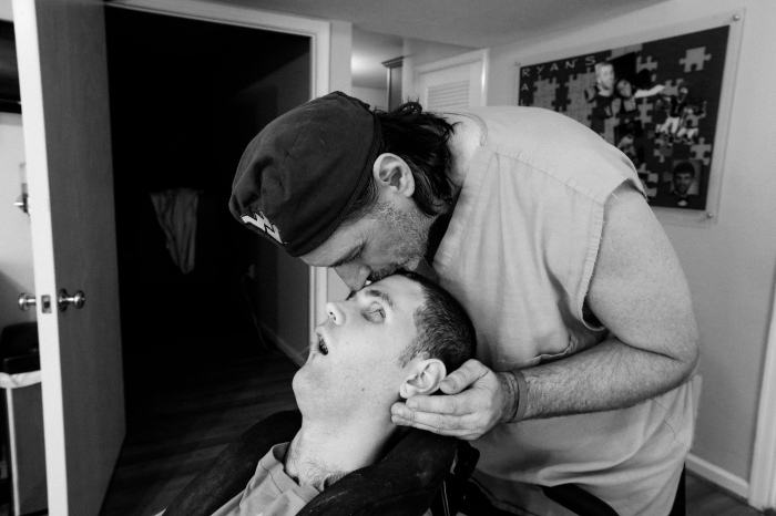 Ashburn, Va -- October 23, 2014 -- Ken kisses the top of Ryan's head during a break from physical therapy. (Kaitlin Newman/Baltimore Sun)