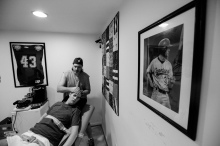 Ashburn, Va -- October 23, 2014 -- Ken exercises Ryan's arms. A portrait of Ryan during his baseball days hangs on the wall, a reminder of Ryan's past self. (Kaitlin Newman/Baltimore Sun)