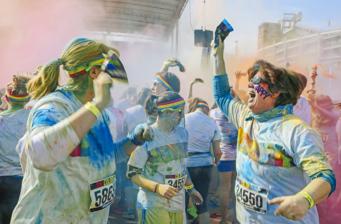 Baltimore, MD -- April 19, 2014 -- Runners celebrate the finish line by dousing each other with powder at the Color Run on Saturday morning. The popular course is a 5K where runners get bombarded with handfuls of colored powder throughout the race. (Kaitlin Newman for Baltimore Sun)