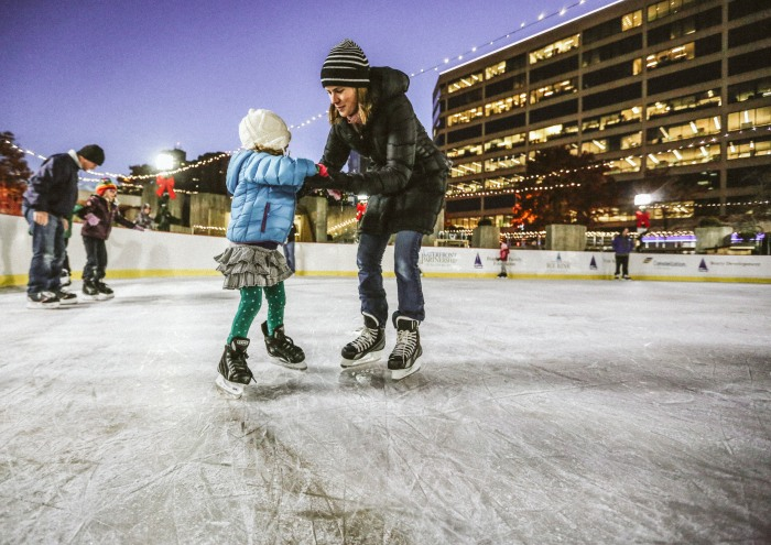 Baltimore, Md -- November 21, 2014 -- Rachel Duncan, 35, and daughter Millicent Grimaldi, 5, help each other at the newly opened rink at McKeldin Sqaure. (Kaitlin Newman for Baltimore Sun)