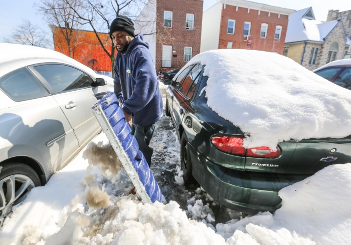 Baltimore, Md — February 22, 2015 — Larontey Gross, 40, shovels out his car following Saturday's storm. (Kaitlin Newman for Baltimore Sun)
