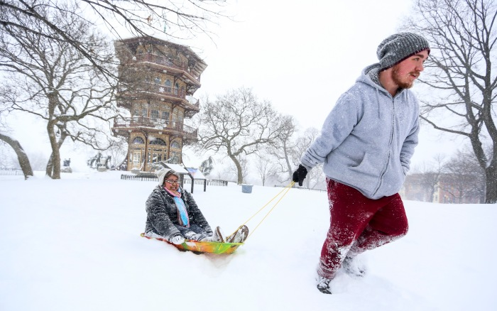 Baltimore, Md — February 21, 2015 — Cara Duldulao, 24, gets a tug from Michael Rager, 23, at Patterson Park during Saturday's snowstorm. (Kaitlin Newman for Baltimore Sun)